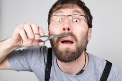 Male barber cuts his own mustache, looking at the camera like the mirror. stylish professional hairdresser expresses Stock Photo