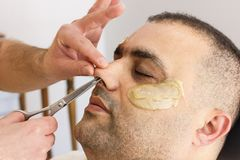 Male barber cutting hairs in the nose by scissors at the adult man in Turkey stock image