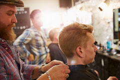 Male Barber Giving Client Haircut In Shop Royalty Free Stock Photography
