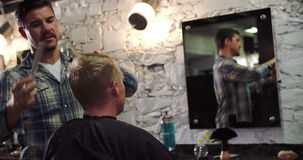 Male Barber Giving Client Haircut In Shop. Hairdresser cutting clients hair as they sit in chair.Shot on Sony FS700 at frame rate of 25fps stock footage