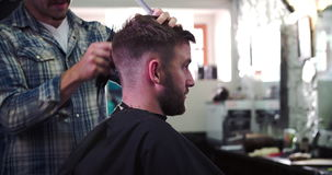 Male Barber Giving Client Haircut In Shop. Hairdresser shaving the back of clients head as they sit in chair.Shot on Sony FS700 at frame rate of 25fps stock video