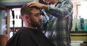 Male Barber Giving Client Haircut In Shop. Hairdresser shaving the side of client's head as they sit in chair.Shot on Sony FS700 at frame rate of 25fps stock footage