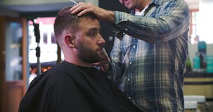 Male Barber Giving Client Haircut In Shop. Hairdresser shaving the side of client's head as they sit in chair.Shot on Sony FS700 at frame rate of 25fps stock video footage
