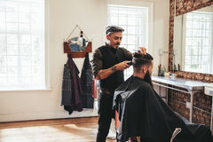 Male barber giving client haircut Stock Photos