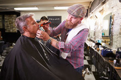 Male Barber Giving Client Shave In Shop Royalty Free Stock Image