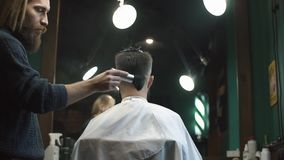 Male barber make a haircut for bearded client and using a talc at barbershop.  stock video footage