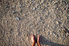 Male bare feet on the beach of the small coral. Top view Stock Photo