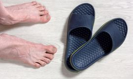 Male Bare Feet and a Pair of Flip Flops. Male bare feet next to a pair of blue flip-flops on a white wooden floor Stock Images