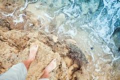 Male bare feet stand on coastal rocks. Travel lifestyle background Stock Photography