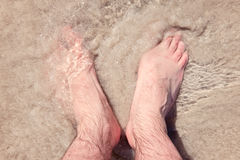 Male bare feet in a warm sand on a sunny beach during vacation. Stock Images