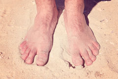 Male bare feet in a warm sand. On a sunny beach during vacation Royalty Free Stock Photos