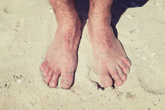Male bare feet in a warm sand on a sunny beach during vacation. Stock Photography