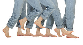 Male Barefoot Legs in Motion. A man takes one step forward in jeans on white stock photography