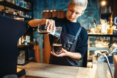 Male barista in apron makes fresh black coffee. Young male barista in apron makes fresh black coffee at cafe counter. Barman works in cafeteria, bartender Stock Photo