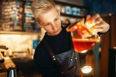 Male barista checks the sediment in the coffee pot. Young male barista in apron checks the sediment in the coffee pot. Barman works in cafeteria, bartender Stock Photo