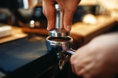 Male barista hands, fresh black coffee preparation. At cafe counter. Barman works in cafeteria, bartender prepares espresso Stock Photography