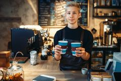 Male barista holds two cups of fresh hot coffee. Male barista holds in hands two cups of fresh hot coffee, cafe counter on background. Professional espresso Stock Photos