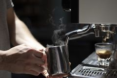 Male barista making espresso at a coffee shop stock images