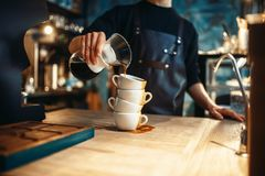 Male barista pours black coffee on a stack of cups. Cafe counter and espresso machine on background. Barman works in cafeteria, bartender occupation Royalty Free Stock Photography
