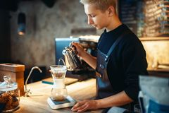 Male barista pours ground coffee into the glass. Standing on the stove. Barman works in cafeteria, bartender occupation Royalty Free Stock Photography