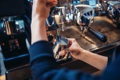 Male barista prepares beverage on coffee machine. In cafe. Professional espresso preparation by barman Stock Photos