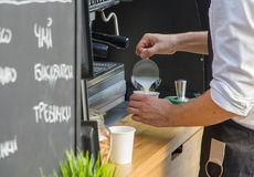Male barista prepares latte. Male barista pours milk in cup to prepare latte Royalty Free Stock Photography