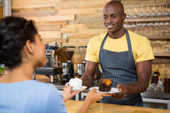 Male barista serving coffee and dessert to female customer. Portrait of male barista serving coffee and dessert to female customer in cafe Royalty Free Stock Photos