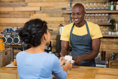 Male barista serving coffee to customer in coffee shop. Happy male barista serving coffee to customer in coffee shop Stock Images