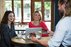 Male barista serving dessert to customers in coffee shop. Male barista serving dessert to female customers in coffee shop Royalty Free Stock Image