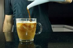 Barista serving iced coffee on a glass cup Royalty Free Stock Photo