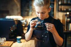 Male barista sniffs fresh prepared black coffee. Young male barista sniffs fresh prepared black coffee, cafe counter on background. Professional espresso Stock Photo