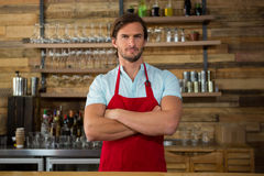 Male barista standing arms crossed in coffee shop. Portrait of male barista standing arms crossed in coffee shop Royalty Free Stock Photos
