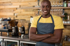 Male barista standing arms crossed in coffee shop. Portrait of smiling male barista standing arms crossed in coffee shop Royalty Free Stock Photos