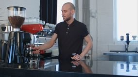 Male barista using the coffee machine preparing coffee for a client. Professional shot in 4K resolution. 091. You can use it e.g. in your commercial video stock image
