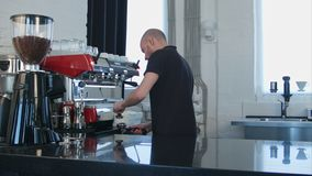 Male barista using the coffee machine preparing coffee for a client. Professional shot in 4K resolution. 091. You can use it e.g. in your commercial video stock video