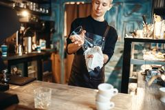 Male barista wipes the dishes after making coffee. Young male barista wipes the dishes after making coffee at cafe counter. Barman works in cafeteria, bartender Royalty Free Stock Images