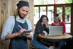Male barista writing orders with female customers in background. At coffee shop Stock Image