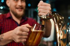 Male barmen poring beer in pint in pub. Selective focus of male hands keeping pint and pouring beer in pub. Young bearded barmen in checkered shirt with tattoo royalty free stock images