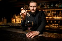 Bartender adds ice cube in alcohol cocktail royalty free stock image
