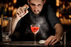 Bartender pours the alcohol cocktail using sprayer royalty free stock photography