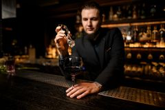Bartender putting ice cube in alcohol cocktail royalty free stock images