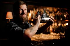 Male bartender with a beard and tattoo on hands holding a steel shaker. On the bar counter in the blurred background of the bar shelves stock photos