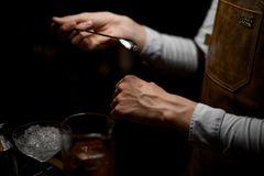 Male bartender holding a spoon and put a drop on the hand. On the bar counter in the dark blurred background stock image