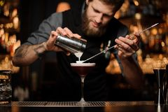 Male bartender makes cocktail using shaker and spoon. Young tattooed male bartender with beard makes red alcohol cocktail using steel shaker and long bar spoon royalty free stock photo