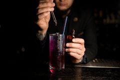 Male Bartender making alcohol cocktail with dropper. Male bartender in suit making tasty alcohol cocktail with straw using dropper stock image
