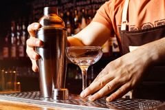 Male bartender is making cocktail holding shaker at bar. Background royalty free stock images