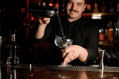 Bartender pouring an alcohol from shaker to glass. Male bartender with mustache pouring an alcohol cocktail from stainless steel shaker to a glass stock photography