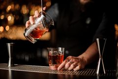 Male bartender pours alcohol cocktail with strainer stock images