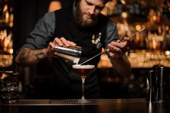 Male bartender pours cocktail using shaker and spoon. Brutal tattooed male bartender with beard pouring red alcohol cocktail using steel shaker and long bar stock image