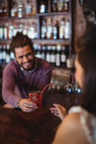 Male bartender serving a cocktail drink to customer at bar counter Royalty Free Stock Photography
